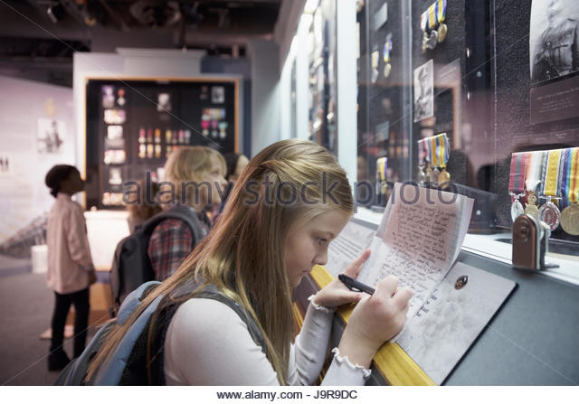 Focused girl student taking notes, writing in notebook at exhibit on field trip in war museum - Stock-Bilder