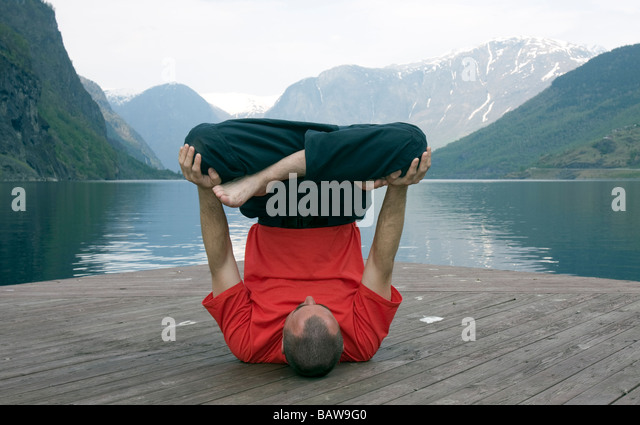 Doug Blane performing an Urdhva Padmasana yoga, upside down lotus on Aurland Fjord, Flam, Norway - Stock Image