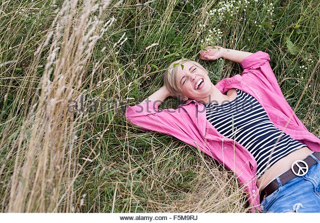 Young woman lying in long grass laughing - Stock Image