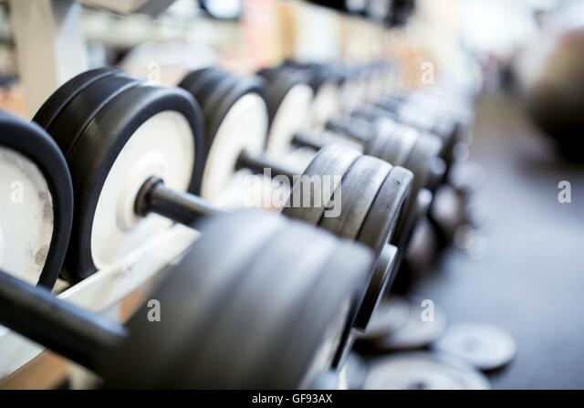 PROPERTY RELEASED. Close-up of heavy dumbbells arranged in row on rack. - Stock Image