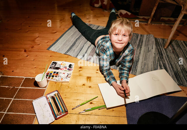 Boy lying on floor with watercolor paints and sketch pad - Stock-Bilder