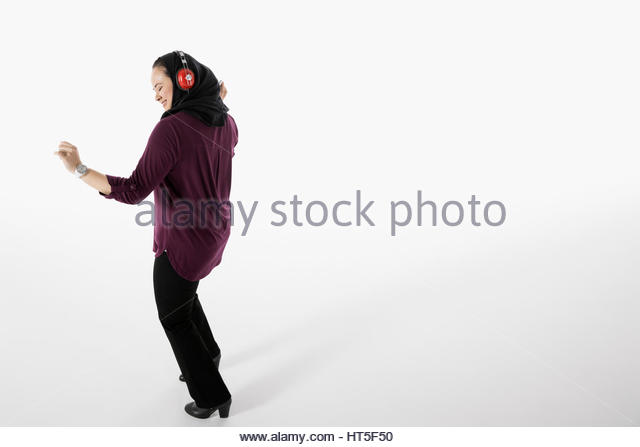 Happy woman in hijab dancing, listening to music with headphones against white background - Stock-Bilder