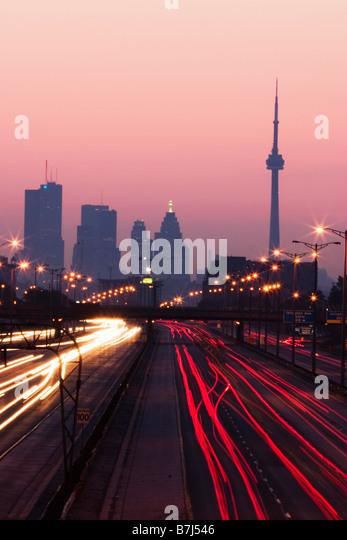 View of Toronto skyline from above Queen Elizabeth Way highway during start of rush hour traffic, Toronto, Ontario, - Stock-Bilder