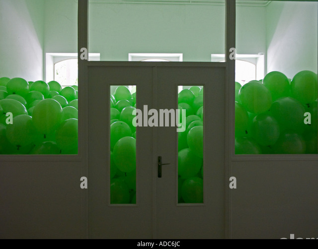 Martin Creed installation green balloons fill a white room - Stock Image