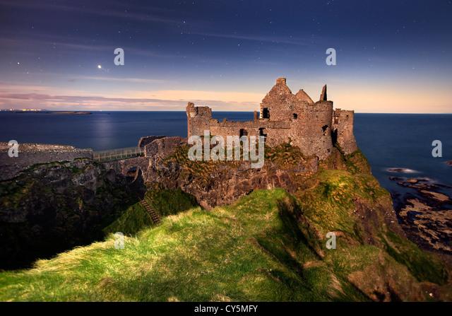 Dunluce Castle captured at night under moonlight. - Stock Image
