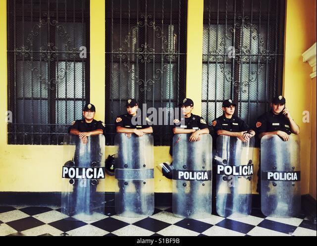 Five policemen standing in the shadow on Plaza de Armas in Lima, Peru - Stock-Bilder