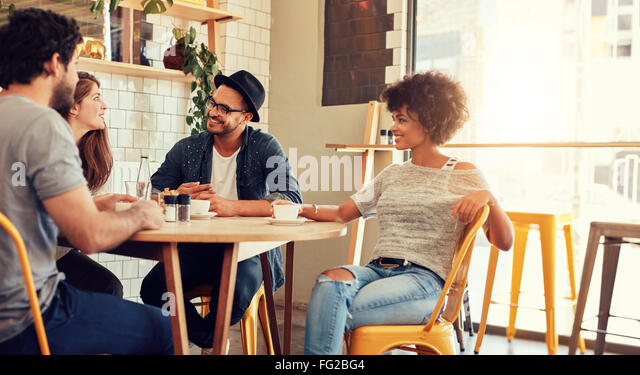 Portrait of a young group of friends meeting in a cafe. Young men and women sitting at cafe table and talking. - Stock-Bilder