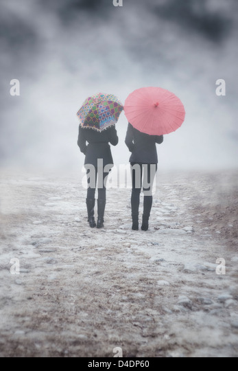 two girls with colourful umbrellas are walking in the mist - Stock Image