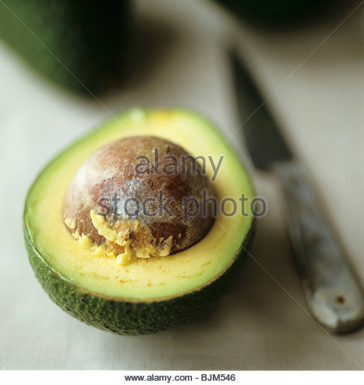 Half an avocado with stone - Stock Image