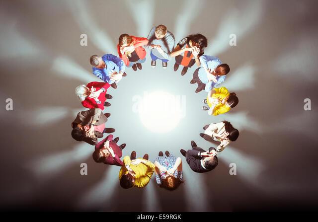 Crowd forming circle around bright light - Stock Image