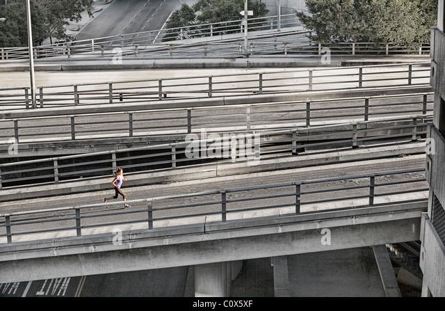 Female runner running on urban city street bridge, overpass in Los Angeles, California - Stock-Bilder