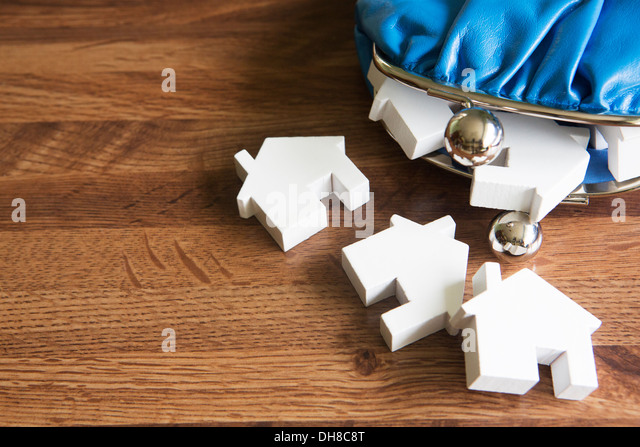 Purse with Model Houses On Wooden Surface - Stock Image