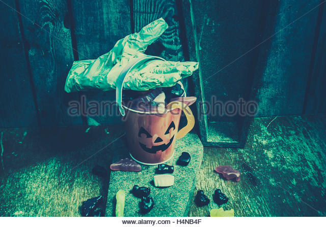 Blue halloween night background on a cute smiling pumpkin bucket being collected by a bandaged mummy hand - Stock Image