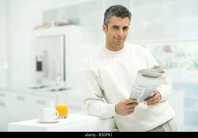 Man leaning against kitchen counter, holding newspaper, smiling at camera - Stock-Bilder