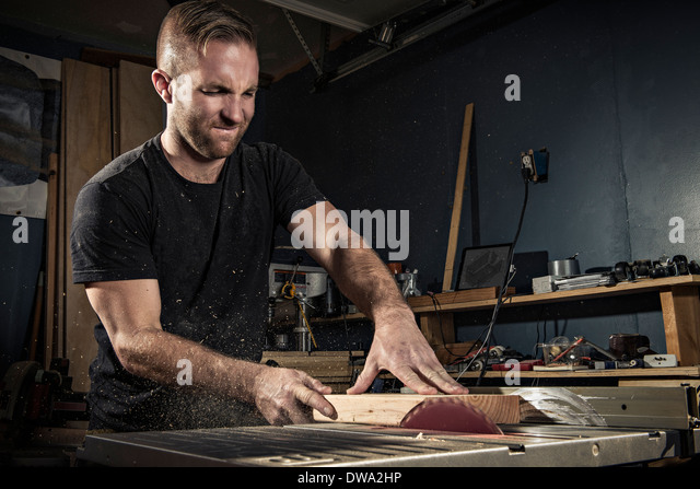Male carpenter using a rotary saw in workshop - Stock Image