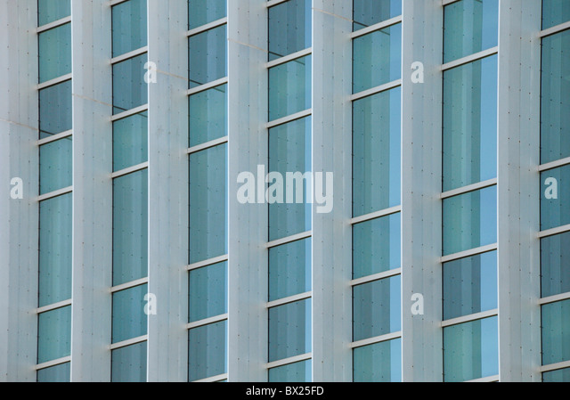 Exterior windows of a modern steel and glass commercial office building reflecting blue sky - Stock Image