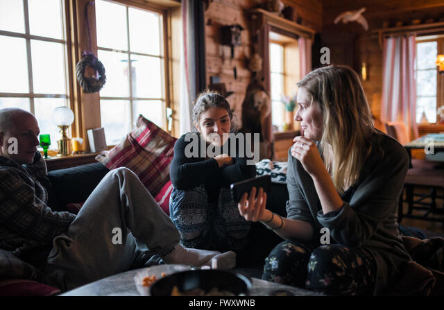 Sweden, Young woman showing smart phone to friends in log cabin - Stock-Bilder