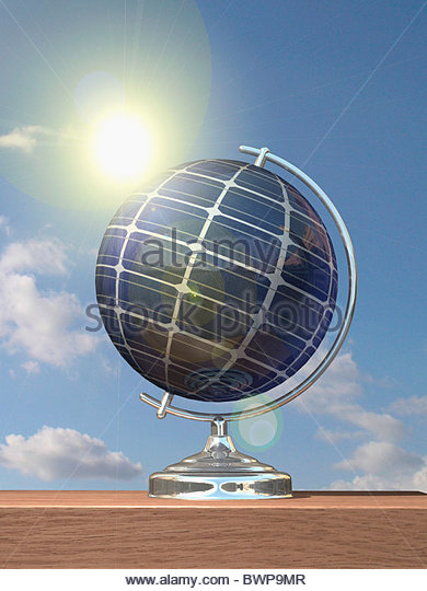 Sun shining on globe covered in solar panels - Stock Image