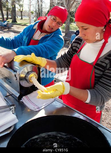 Street vendors preparing dough pastry to make a Churros, Colonia del Sacramento, Uruguay, South America - Stock Image
