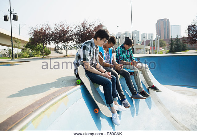 Teenage boys sitting at edge of skateboard ramp - Stock Image