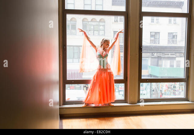 Dancer in dance studio. A woman posing at a window. - Stock Image