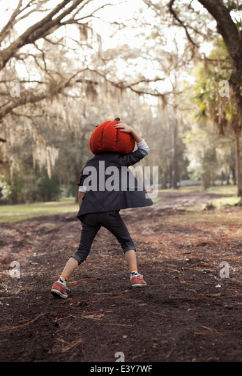 Boy running in forest holding onto pumpkin head - Stock Image