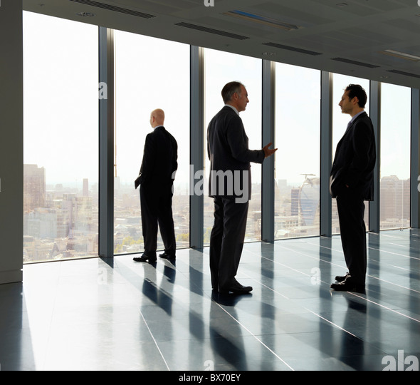 Three executives standing by window in empty office space with view over city landscape - Stock Image