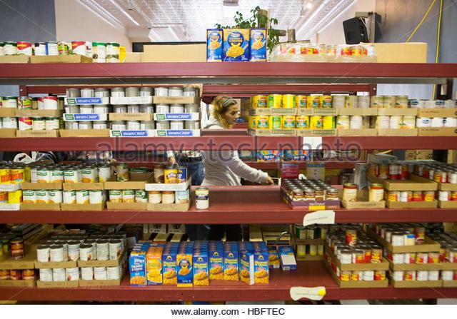 A woman chooses food at the Jordan River Food Pantry. - Stock Image