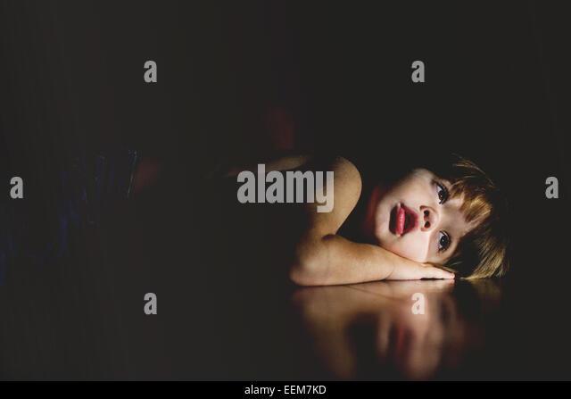Studio shot of boy (2-3) lying on black floor - Stock Image