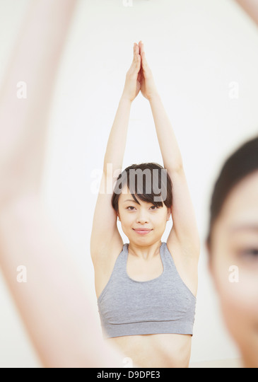 Woman with arms raised and hands together - Stock Image