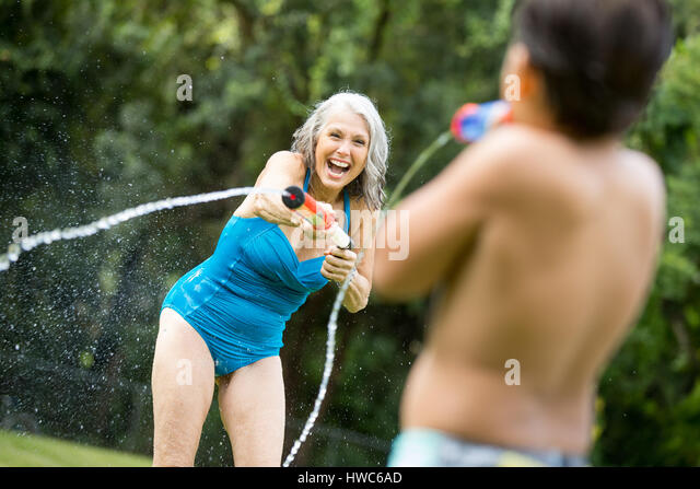 Senior playing in the backyard with grandchild - Stock Image