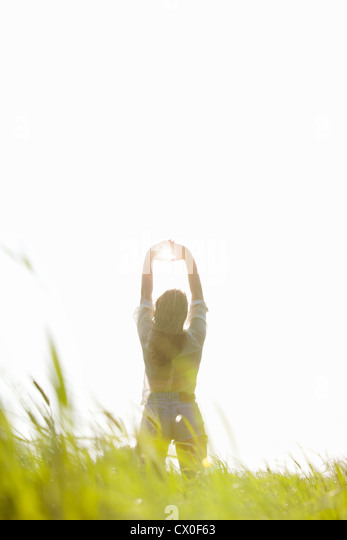 Back View of Woman Standing in a Field with Sun Shining through her Hands - Stock Image