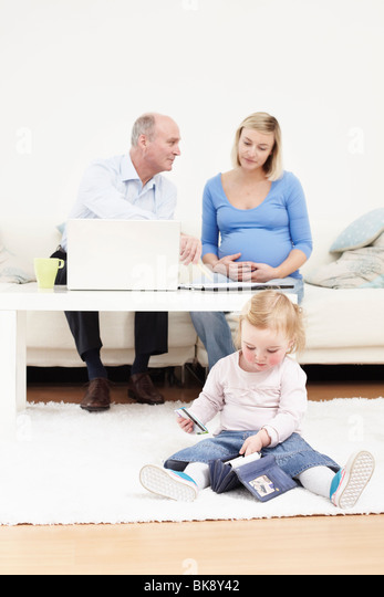 Toddler taking cards out of a purse - Stock Image