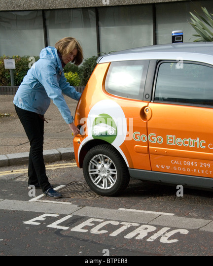 Woman plugging in electric vehicle EV at free EV parking bay South Bank London UK GoGo Electric Vehicle rentals - Stock Image