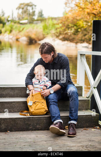 Full length of father searching something in backpack while sitting with baby girl on steps at lakeshore - Stock Image