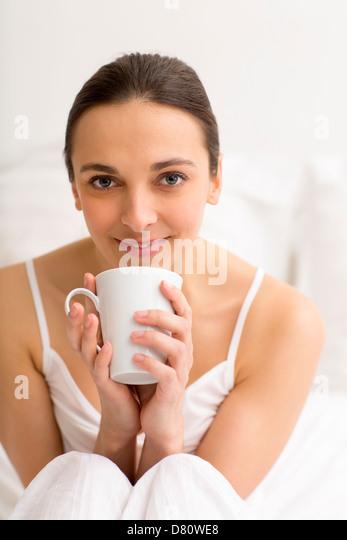 Portrait female enjoying tea in white bedroom - Stock Image