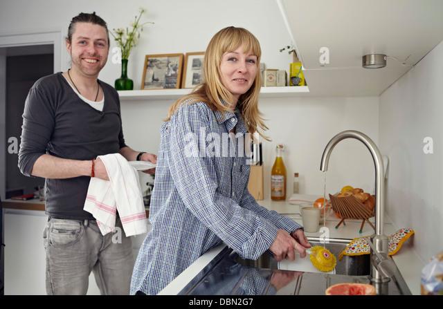 Couple Washing Up In Kitchen - Stock-Bilder