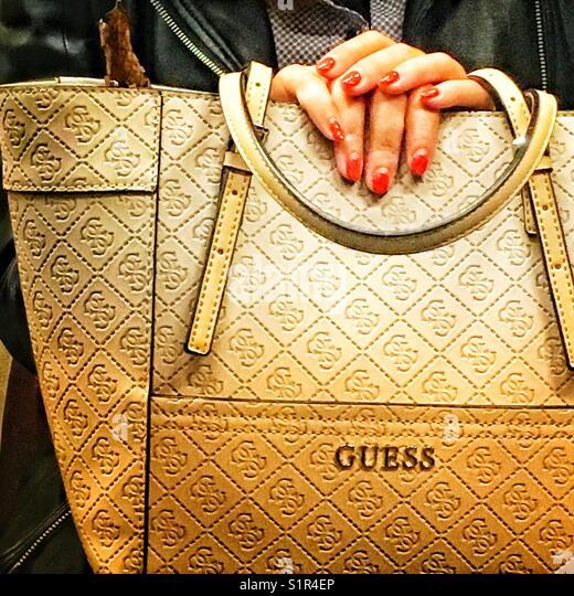 Woman hands on Guess handbag - Stock Image