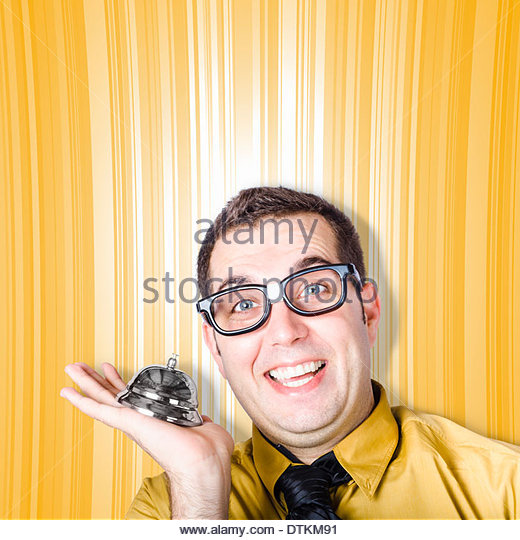 Funny IT helpdesk employee holding desk service bell, ready to assist you with your enquiry - Stock Image