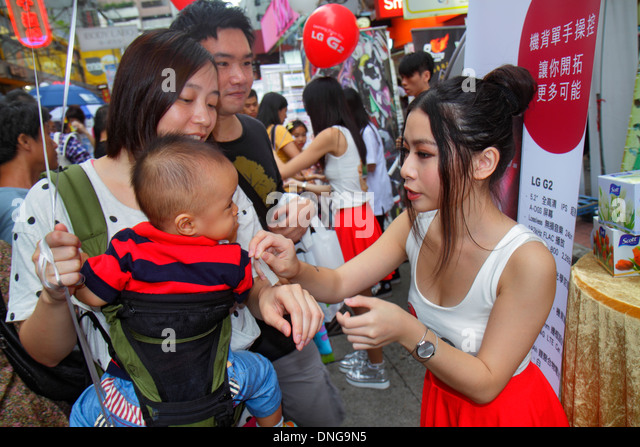 Hong Kong China Kowloon Mong Kok Nathan Road promotion new product representative Asian woman LG G2 Android smartphone - Stock Image
