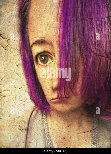 Portrait of woman with purple hair, large head and wide eyed - Stock Image