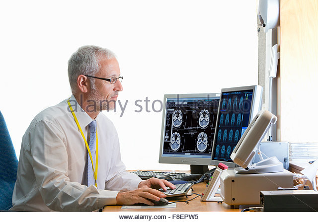 Doctor reviewing digital brain scan in doctor - Stock Image