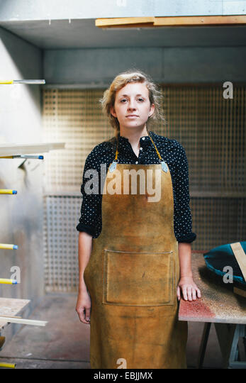 Portrait of young craftswoman in organ workshop - Stock Image