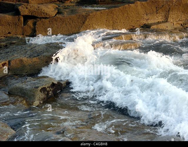 Waves splashing on rocks in early morning sun. - Stock Image