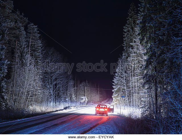 Stationary car with open door on snowy, rural road, at night - Stock Image