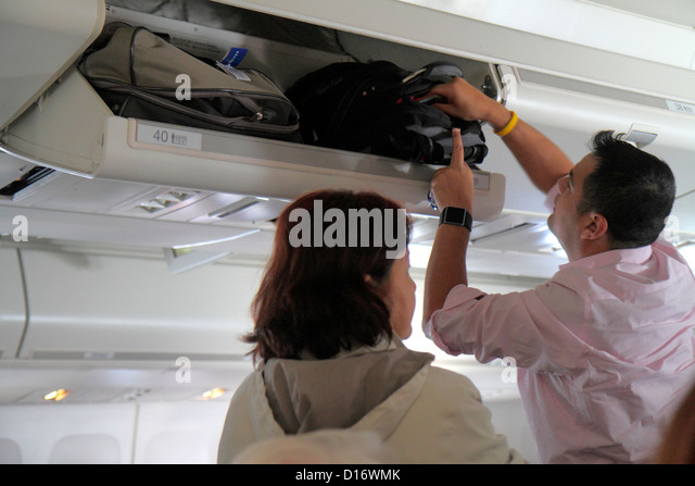 Chicago Illinois O'Hare International Airport ORD onboard United commercial airliner cabin man overhead luggage - Stock Image