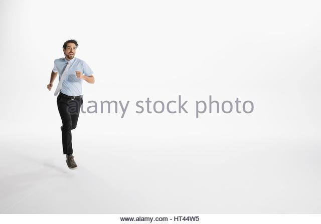 Enthusiastic businessman running against white background - Stock-Bilder