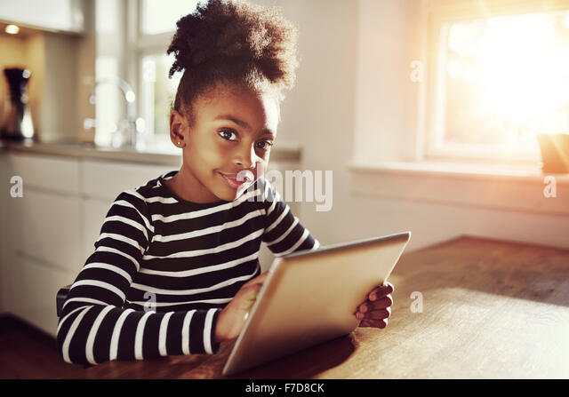 Thoughtful young black girl sitting watching the camera with a pensive expression as she browses the internet on - Stock-Bilder
