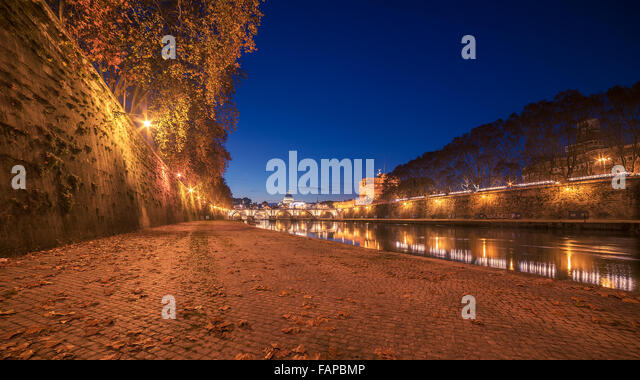 Autumn leaves on embankment of Tiber River in Rome, Italy - Stock Image
