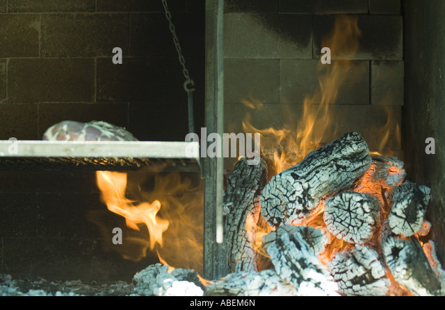 Meat grilling in wood oven - Stock Image
